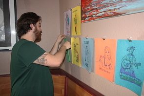 Evan Van Reekum prepares for the April 24 fundraiser  by hanging Roger's Pass artwork on the walls. Photo by Richard Amery