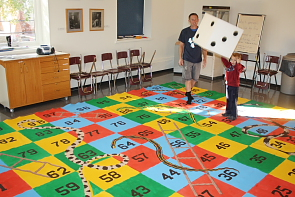 Fawkes Marquis Bruinsma plays a giant game of Snakes and Ladders at the Galt Museum. Photo by Richard Amery