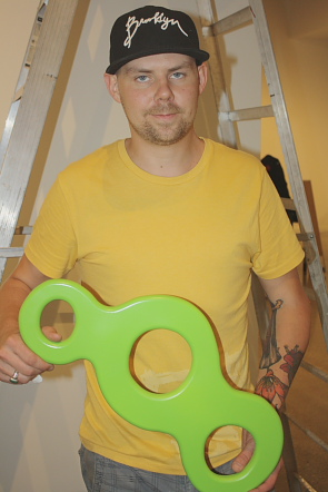 Ryan Smitham holds one of his sculptures for his exhibit New Sculpture. photo by Richard Amery