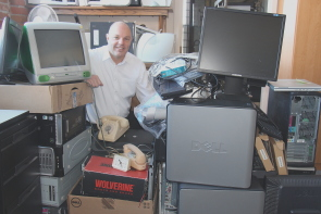 Allan Schneider sits beside some of  the items donated during last year's E-Cycle . Photo by Richard Amery