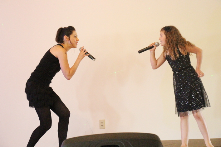 Andi Roberts sings with her daughter. Photo by Richard Amery