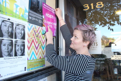 Muffy McKay puts a poster up outide the Allied Arts Council. Photo by Richard Amery