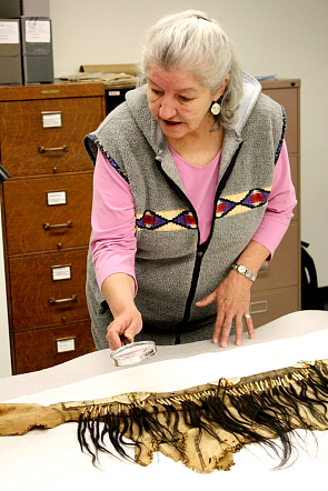 Blanche Bruisedhead uses a magnifying glass to examine the designs on one of the shirts. Photo By Richard Amery
