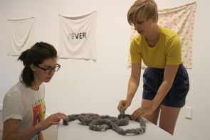 April Matisz and Laura Ajayi set up their exhibit at Casa. Photo by Richard Amery