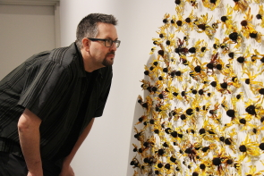 Darcy Logan examines a piece from Cultivating Creativity at Casa. photo by Richard Amery