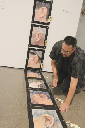 Darcy Logan tweaks a piece in the Disasembled & Catalogued Identity exhibit at CASA. Photo by Richard Amery