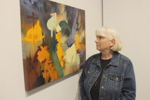 Jeanne Kollee examines one of her paintings in Unter Dem Messer at Casa. Photo by Richard Amery
