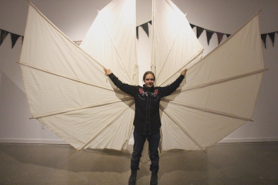 Artist bekk QWells demonstrates how home made wings work in his new exhibti, opening, Sept. 17 at Casa. Photo by Richard Amery