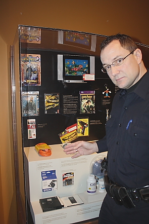 Cst. Blaine Stodolka stands by a case of fake merchandise. Photo by Richard Amery