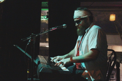 Gabe Thaine playing keyboards with his band at the Slice. photo by Richard Amery