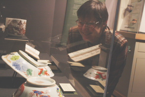 Wendy Aitkens examines three pots from the Chinese National Museum. photo by Richard Amery