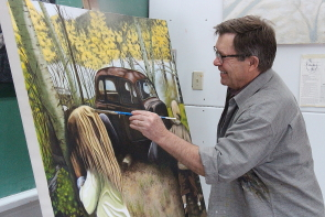 Rick Gillis touches up one of his works at the McNally Studio. Photo by Richard Amery