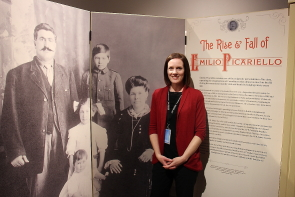Aimee Benoit stands with a family portrait of the Picariello family which opens the Galt Museum's exhibit the Rise and Fall of Emilio Picariello. Photo by Richard Amery