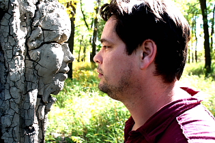 "Artist Troy Nickle examines ""A Woman in the Woods."" Photo By Richard Amery"