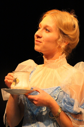 Cecily Cardew played by  Jacqueline Halase, sips some tea during U of l's production of the Importance of Being Earnest, Nov. 22-26 at University Theatre. Photo by Richard Amery
